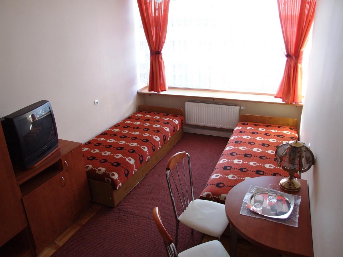 Zdjęcie pokoju dwuosobowego z TV, lodówką oraz WC