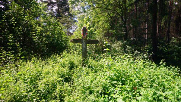 Kamienny krzyż wśród bzów