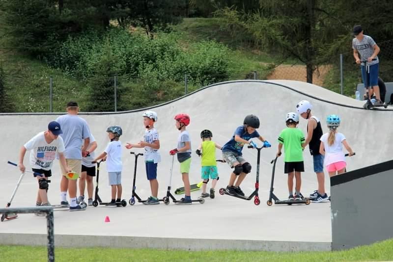 Dzieci jeżdżą na rolkach po skateplazie